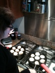 Mom's got her hands full with two aebleskiver pans.